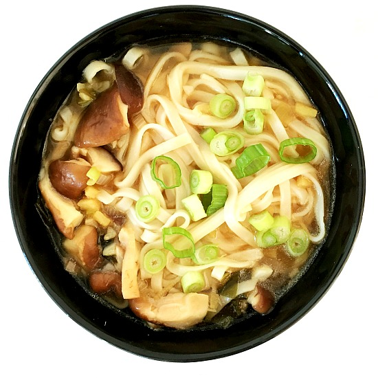 Overhead shot of a black bowl of Japanese udon noodle soup