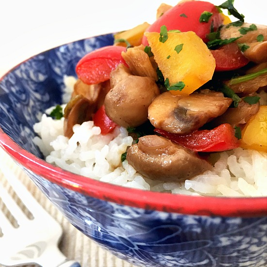 Close-up shot of a blue bowl of mushroom stir fry with rice