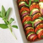 A dish of ratatouille tian and a sprig of fresh basil next to it