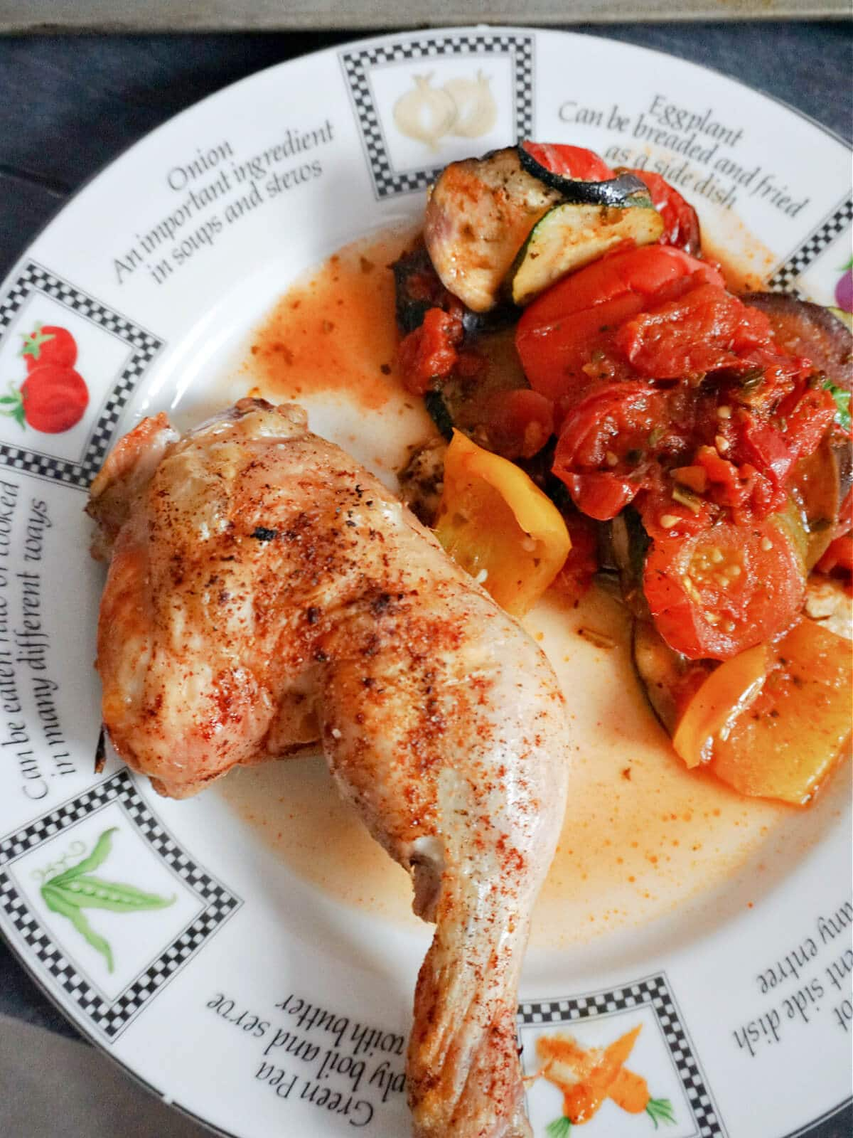 Overhead shot of a plate with a roasted chicken leg and ratatouille
