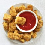 Overhead shot of a white plate of chicken nuggets with a rameskin of ketchup in the middle of it