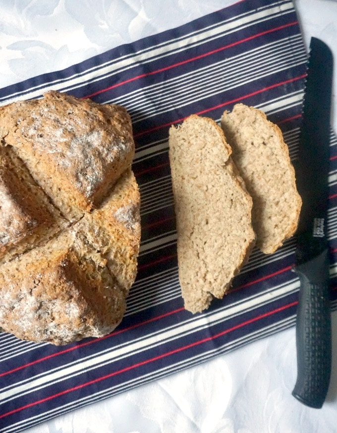 Overhead shot of 2 slices of traditional Irish soda bread next to the bread, and a bread knife