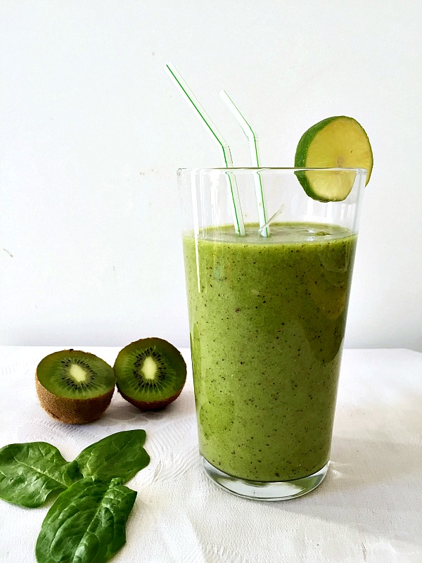 A glass of lime kiwi spinach smoothie with 2 straws in and a slice of lime