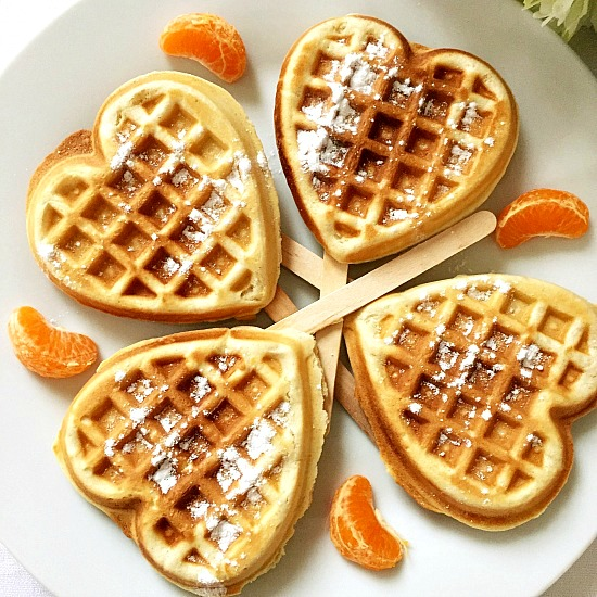 4 heart-shaped cinnamon waffles on a white plate