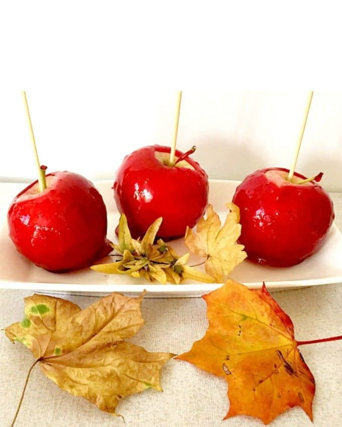 2 red candy apples on a white plate with yellow leaves around them