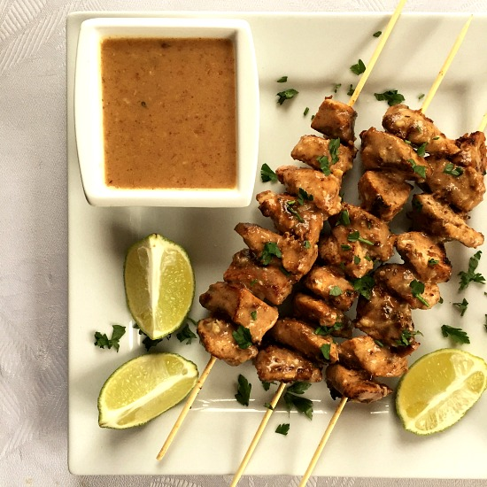 Overhead shoot of a white plate with chicken stay skewers, a bowl of peanut sauce and 3 lime wedges