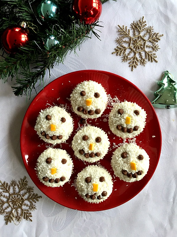 Overhead shoot of a red plate with 7 snowman cupcakes