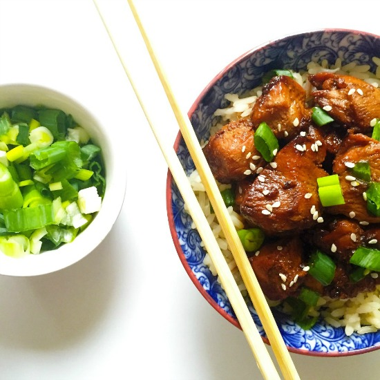 Overhead shot of a blue bowl of grilled teriyaki chicken topped with chopped spring onions and chopsticks on the side and a small bowl of chopped spring onions