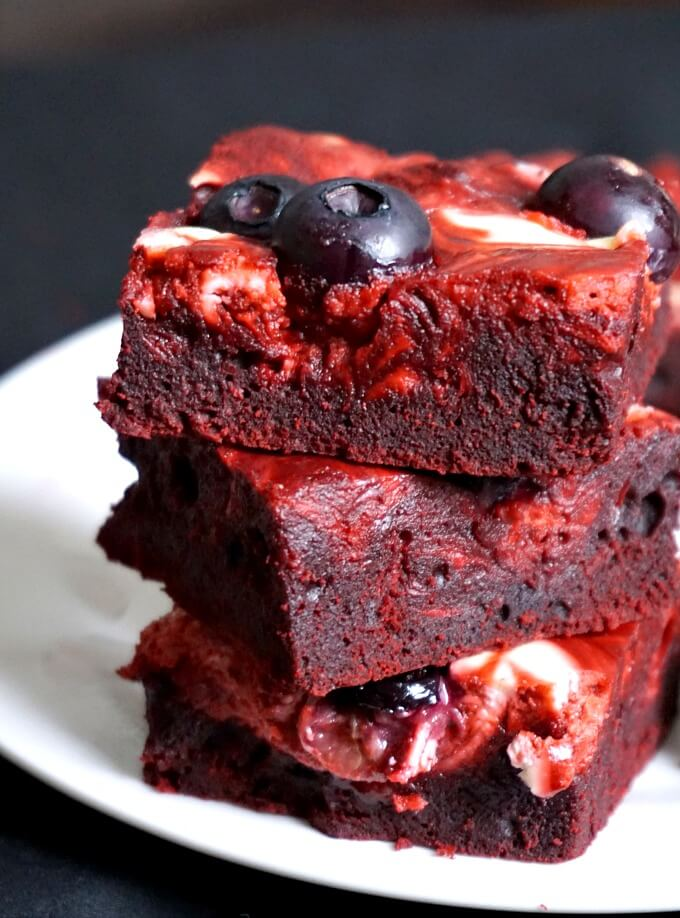 A stack of 3 red velvet cheeesecake swirl brownies with blueberries on a white plate