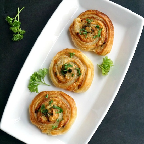 overhead shoot of 3 cheese and ham pinwheels on a white rectangle plate