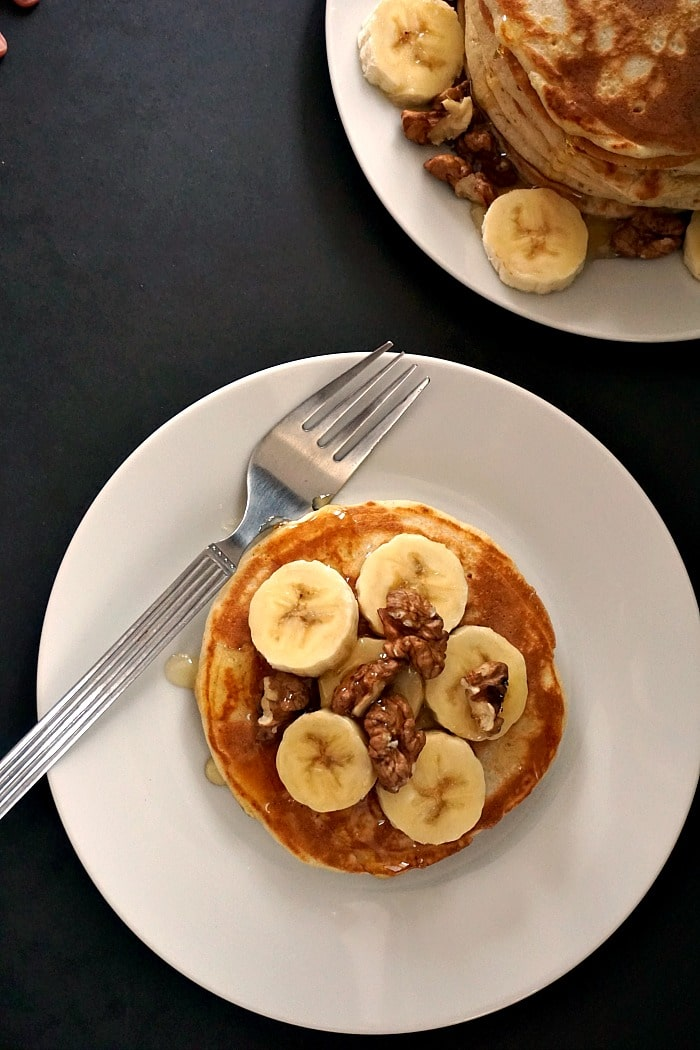 Overhead shoot of a white plate with an American pancake topped with slices of banana and walnuts
