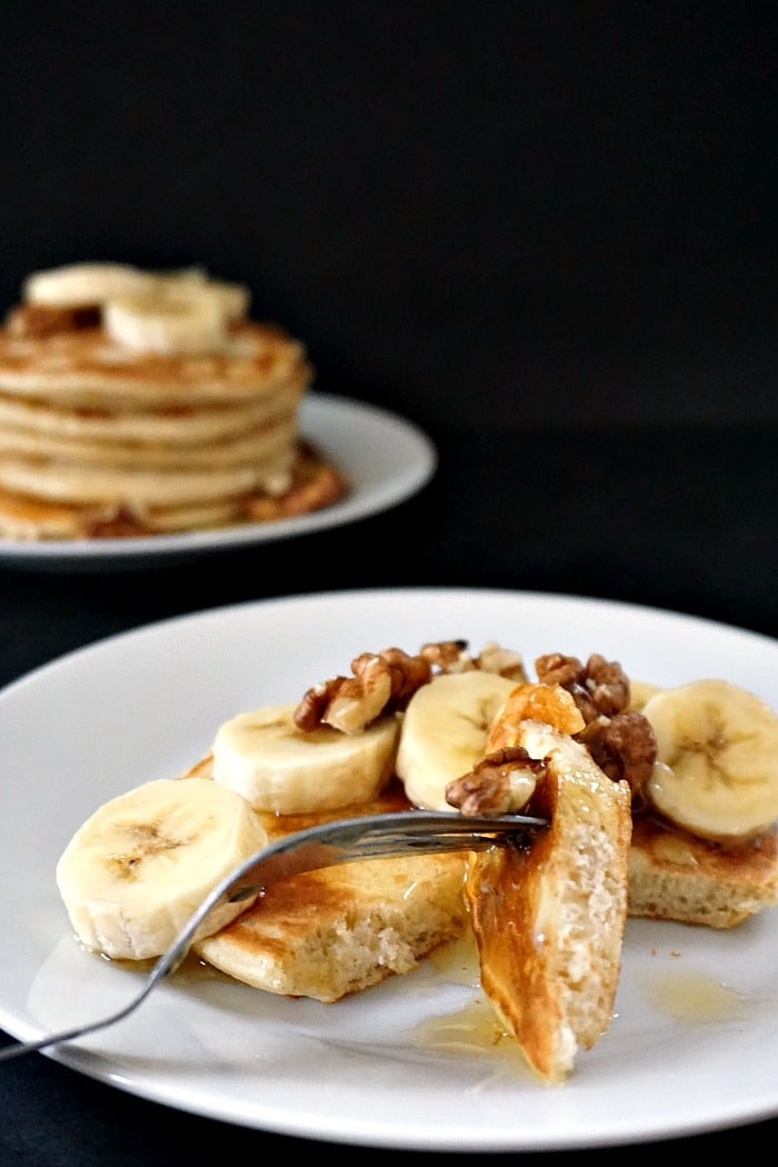 A white plate with pancakes walnuts and banana slices