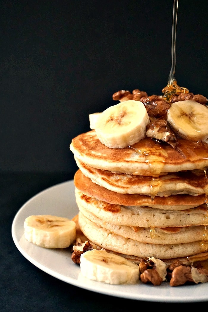 A pile of american pancakes topped with walnuts and bananas