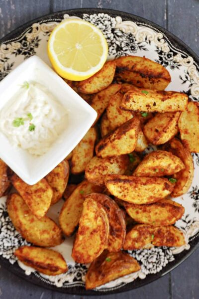 Overhead shoot of a plate with paprika potato wedges, a small bowl of mayo and half a lemon