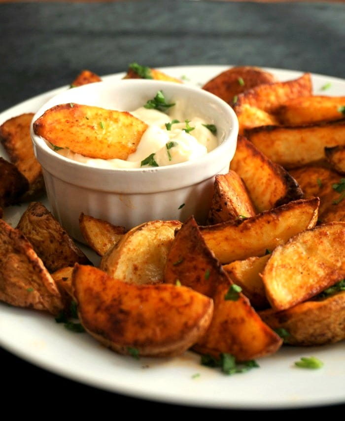 A white bowl of garlic sauce and potato wedges around it