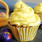 A cupcake topped with lemon icing and creme eggs around it