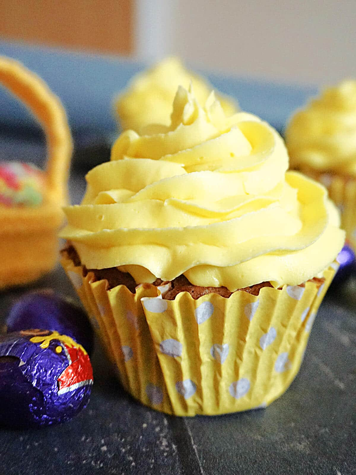 A creme egg cupcake topped with lemon buttercream and creme eggs around it