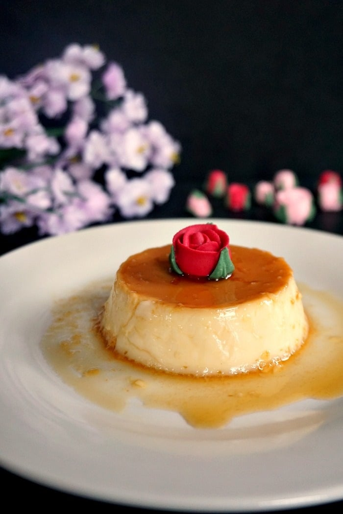 A white plate with a flan topped with a sugar rose