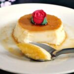 A flan on a white plate with a teaspoon slicing it