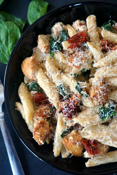 Half a plate of chicken alfredo with sun-dried tomatoes and spinach