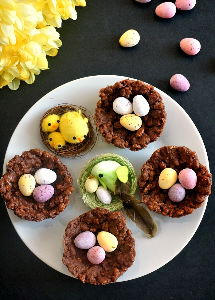 overhead shoot of a white plate with 4 chocolate rice krispie easter nests