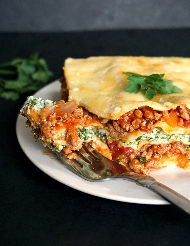 Turkey, spinach and ricotta lasagna on a white plate with a fork on it