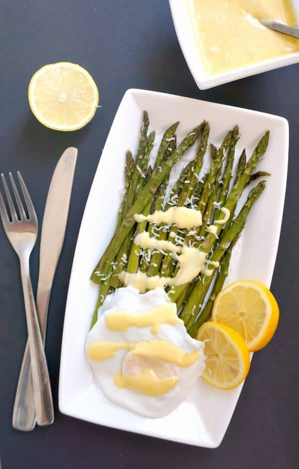 Overhead shoot of a white plate with Roasted Asparagus with Hollandaise Sauce and Poached Egg