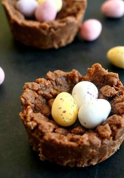 2 chocolate rice krispie Easter egg nests with chocolate easter eggs around
