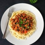 Overhead view of a white plate with spaghetti and turkey bolognese