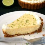 A slice of key lime pie with condensed milk on white plates with a lime slice and a key lime pie in the background