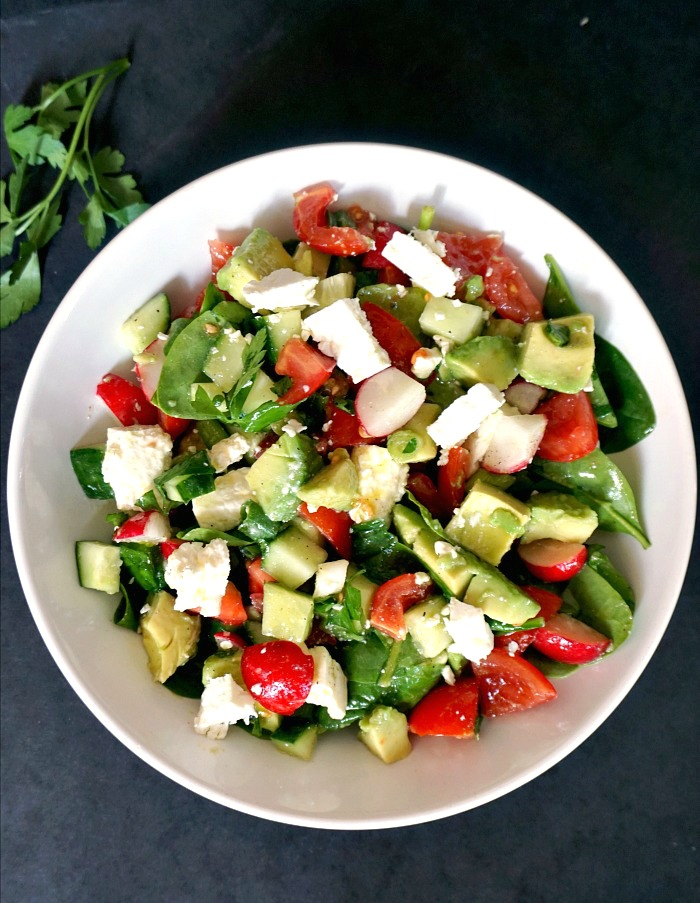 Overhead view of a white plate with summer salad