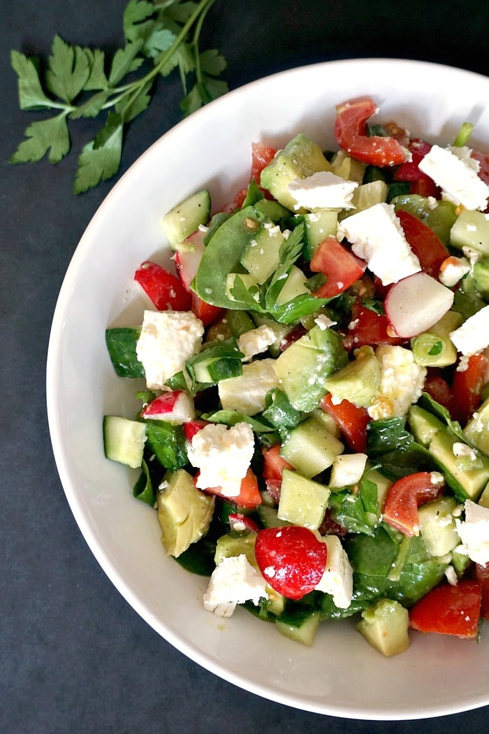 Overhead shoot of a white plate with cucumber tomato avocado feta salad
