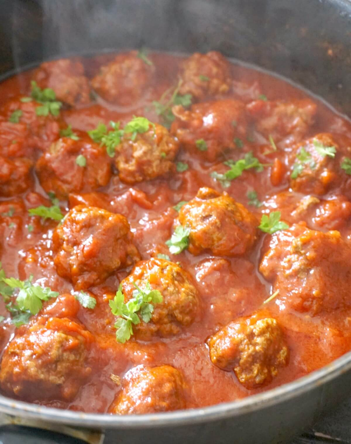 A pot with meatballs in tomato sauce garnished with chopped parsley