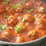 A pot of meatballs in tomato sauce and parsley