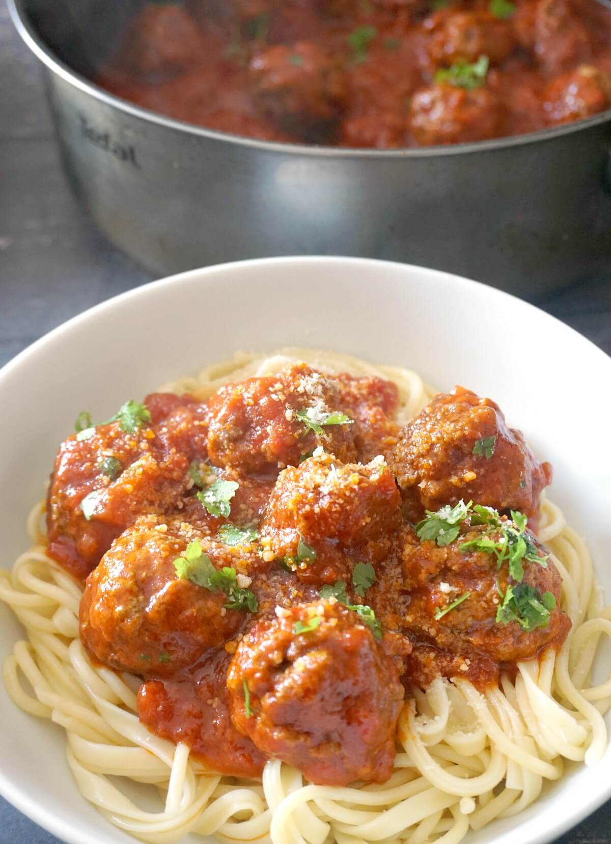 A while bowl with spaghetti topped with meatballs in tomato sauce