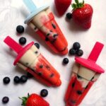 Overhead shoot of 3 red white and blue popsicles with blueberries and strawberries scattered around