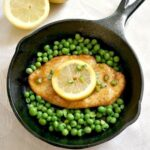 An iron cast skillet with a chicken breast topped with a lemon slice and peas around it