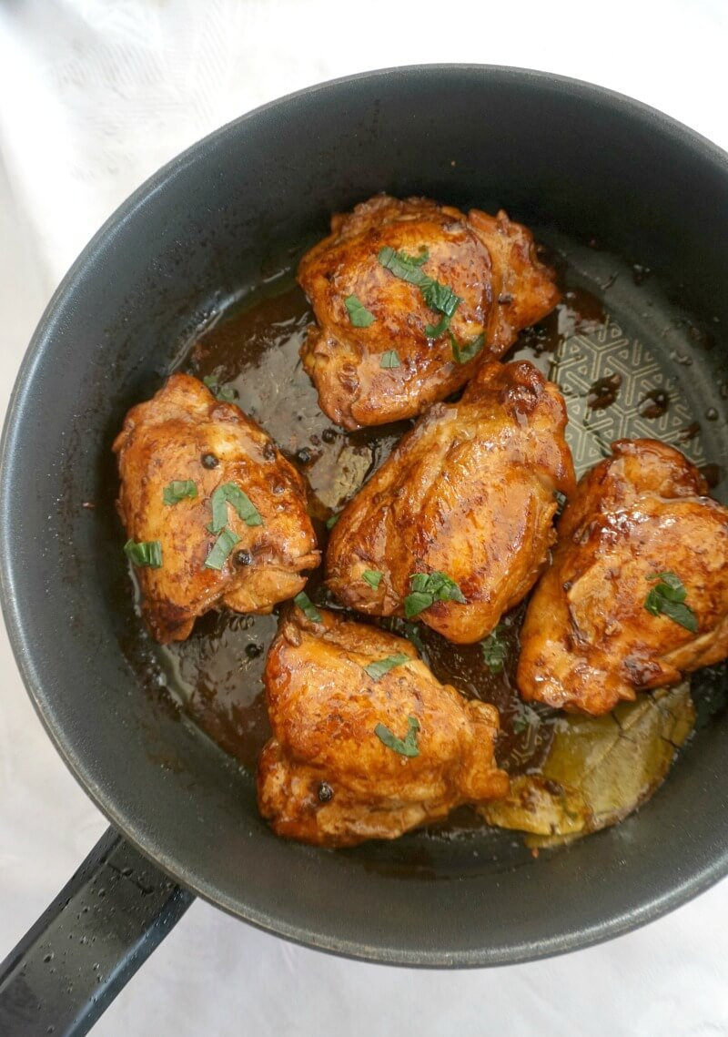 Overhead shot of a pan with cooked chicken adobo thighs