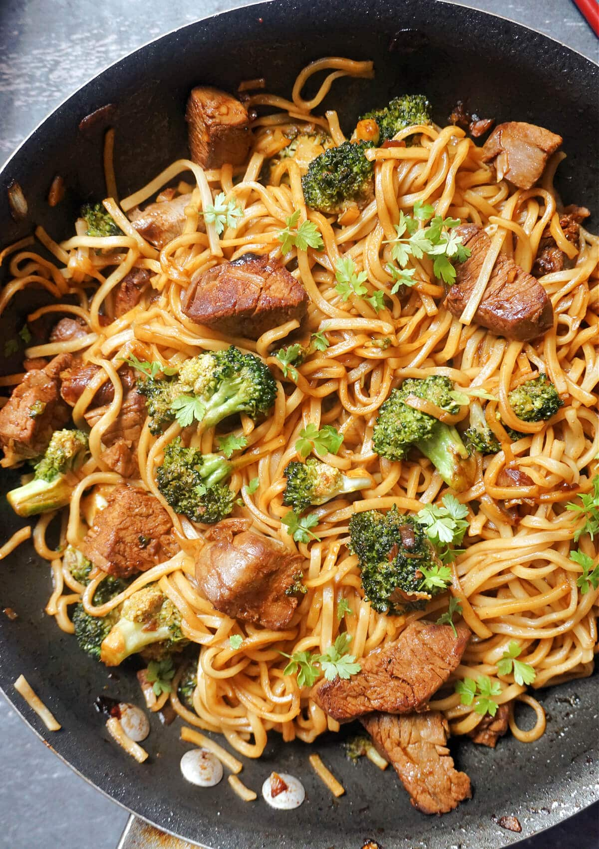 A wok with noodles beef and broccoli
