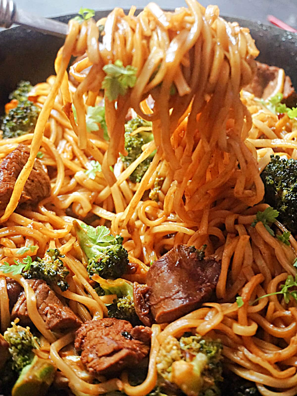 A forkful of noodles off a wok with noodles beef and broccoli stir fry