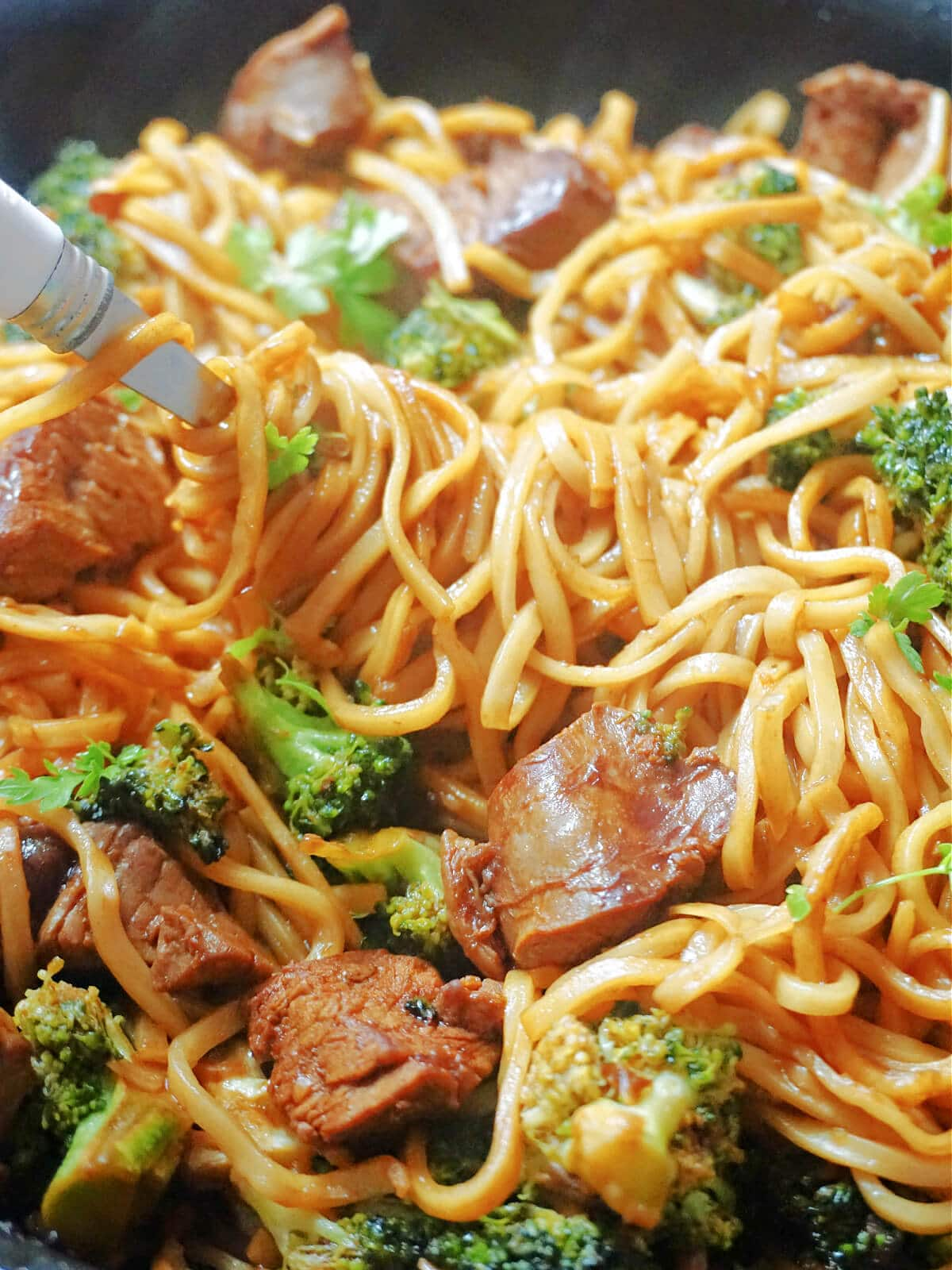 Close-up shot of a noodle stir fry with beef and broccoli
