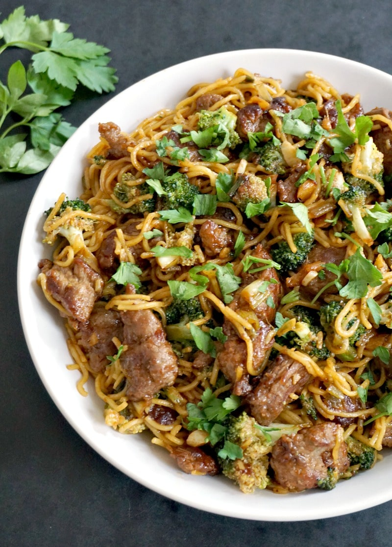 Half of a white plate with beef and broccoli noodles stir fry