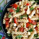 A black plate with chicken pasta salad