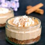 A small pot with sweet pototo cheesecake topped with cream and cinnamon