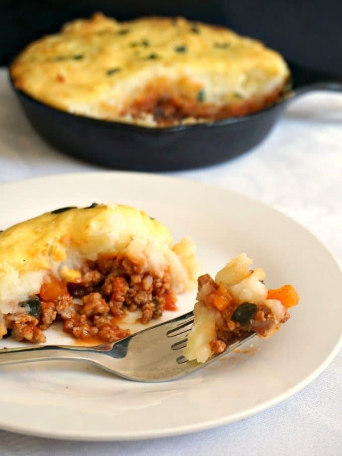 A white plate with cottage pie and a fork with a skillet on the background