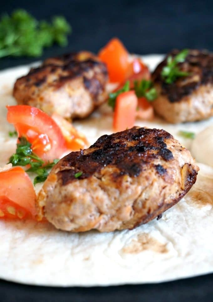 3 turkey kofta on a tortilla wrap with slcied tomatoes and parsley