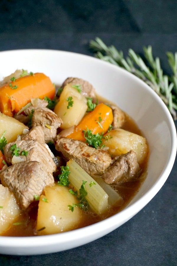 A white bowl of oven beef stew with a rosemary sprig in the background
