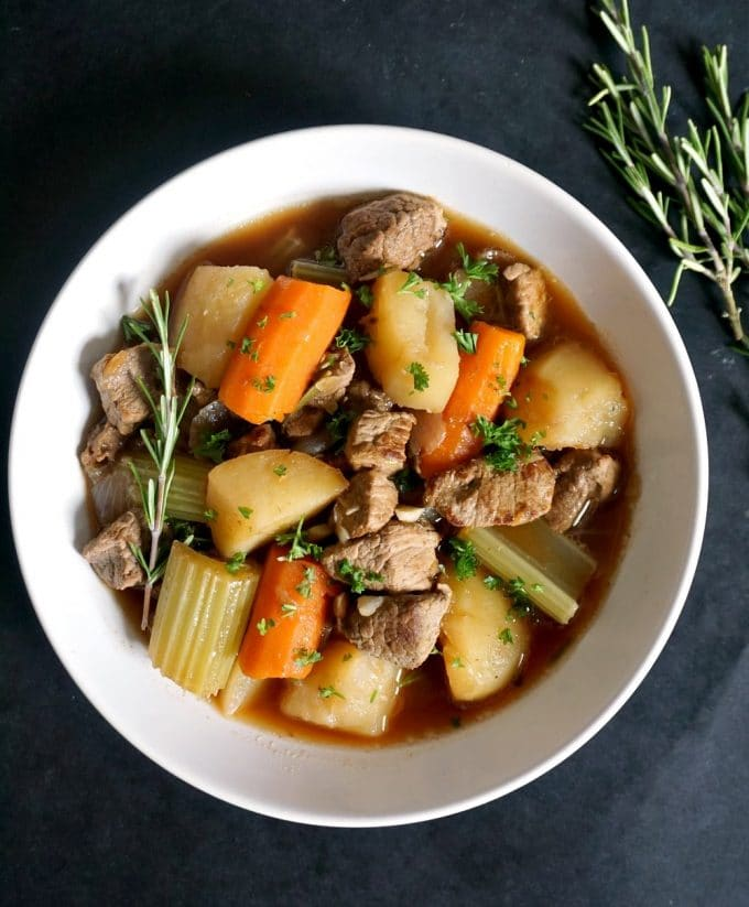 Overhead shot of a white bowl of oven beef stew with a rosemary sprig on the side