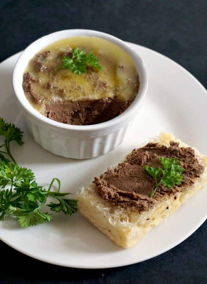 A white plate with a rameskin of quick chicken liver pate, a slice of bread with chicken liver pate spread onto it, and some parsley leaves next to it