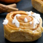A pumpkin pie cinnamon roll with 2 cinnamon sticks and a pumpkin in the background